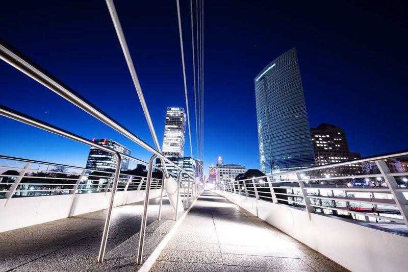 Illuminated modern buildings against clear blue sky in city