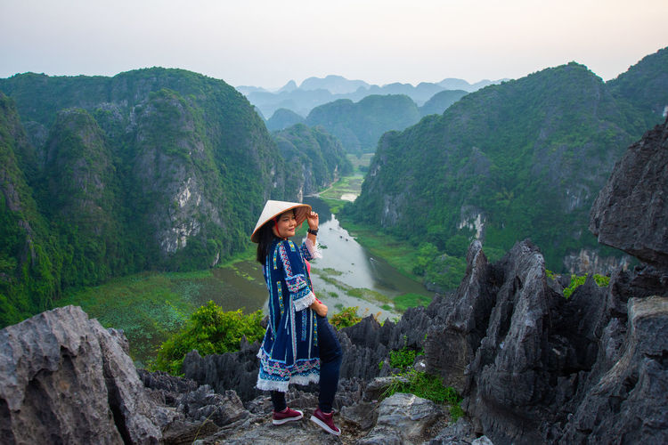 Smiling woman looking away while standing against mountains