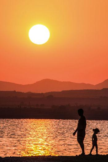 Silhouette men on sea against orange sky