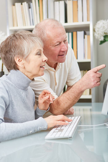 Man and woman using smart phone while sitting on table