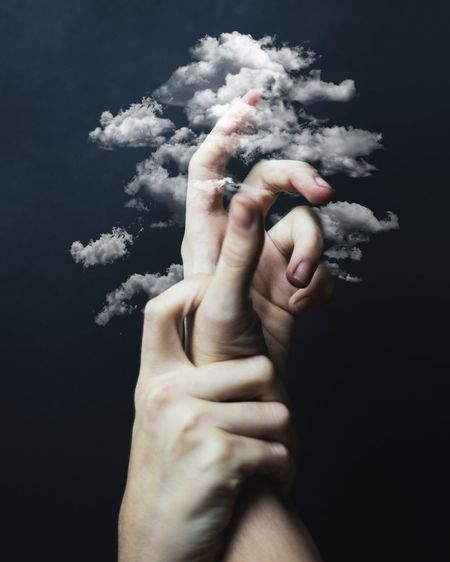 Digital composite image of hands amidst clouds