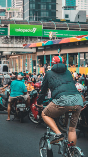 Rear view of people riding bicycle on city street