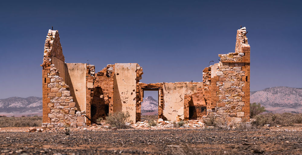 Abandoned built structure at desert against clear sky