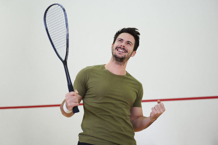 Low angle view of happy mid adult man holding racket while standing by wall in court