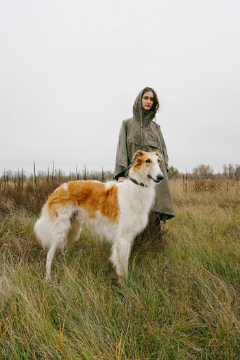 Domestic Animals Field Animal Themes Grass Animal Pets Land Real People Lifestyles Young Adult Leisure Activity Outdoors Pet Owner Nature Hunter Hunters Hunting Dog Raincoat Sad Naturelovers Autumn Autumn colors Fall Young Women Woman