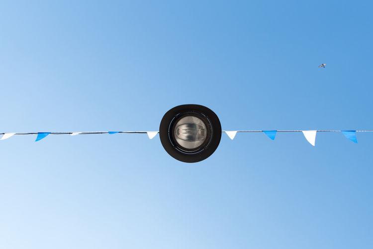 Directly Below Shot Of Street Light Against Blue Sky