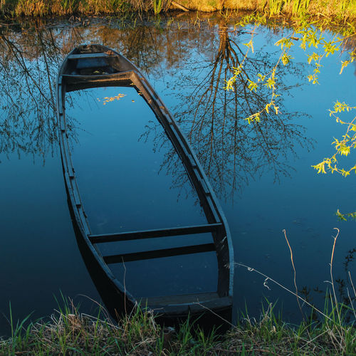 Abandoned boat in pond