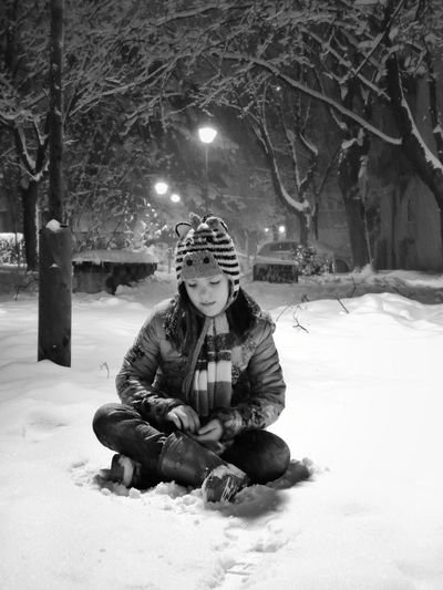 Portrait of boy sitting on snow covered tree