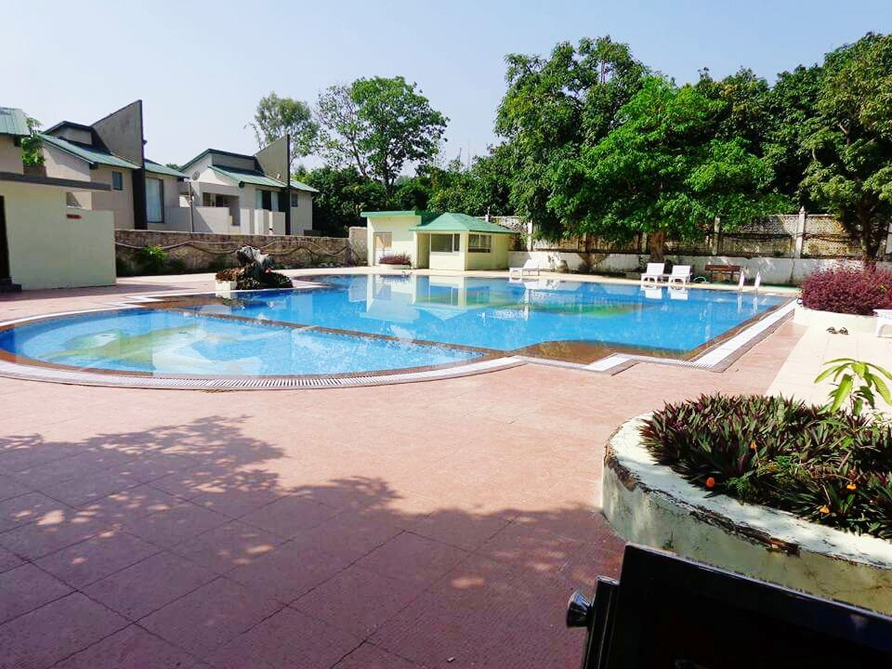 swimming pool, water, outdoors, day, building exterior, architecture, tree, sunlight, shadow, no people, luxury, nature, sky