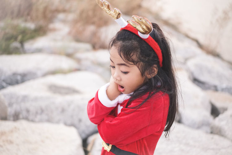 High angle view of girl wearing red dress and headband with mouth open standing on rocks