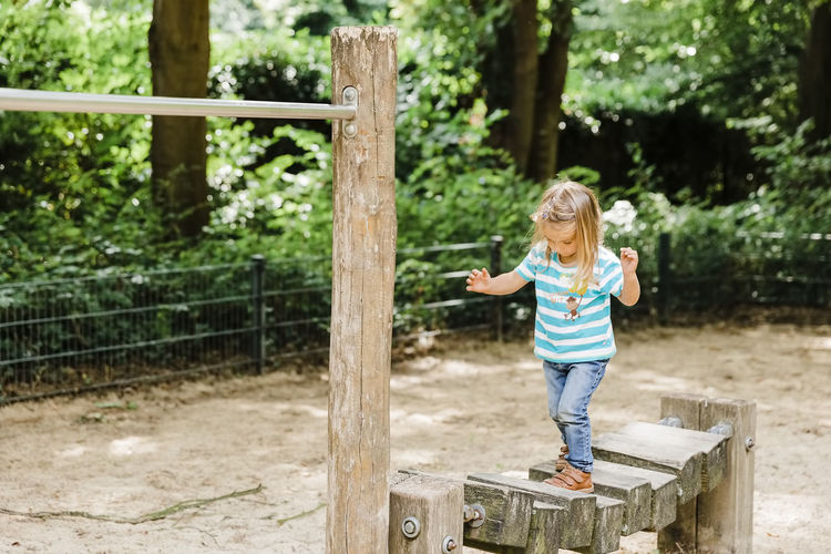 Full length of girl standing standing on play equipment in playground