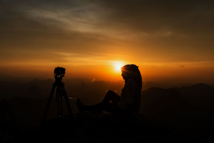 Woman Sitting By Tripod On Mountain Against Orange Cloudy Sky