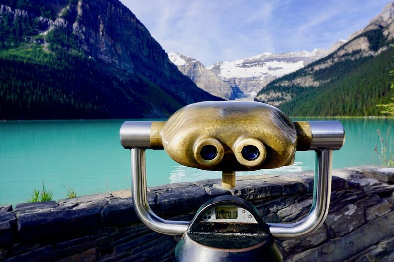 Close-up of coin-operated binoculars by lake against mountains