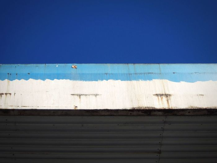 Low Angle View Of Old Garage Against Clear Blue Sky