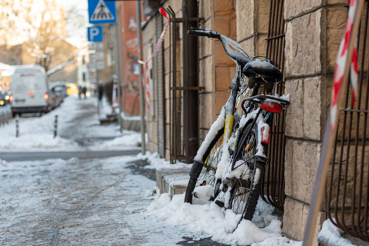Bicycle on street amidst buildings during winter