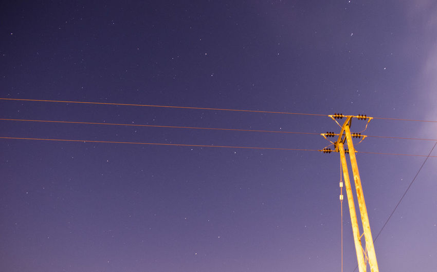 Low angle view of telephone pole against star field at dusk
