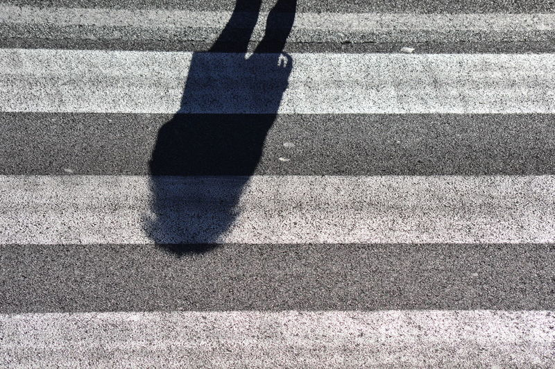 Low section of person on zebra crossing on road