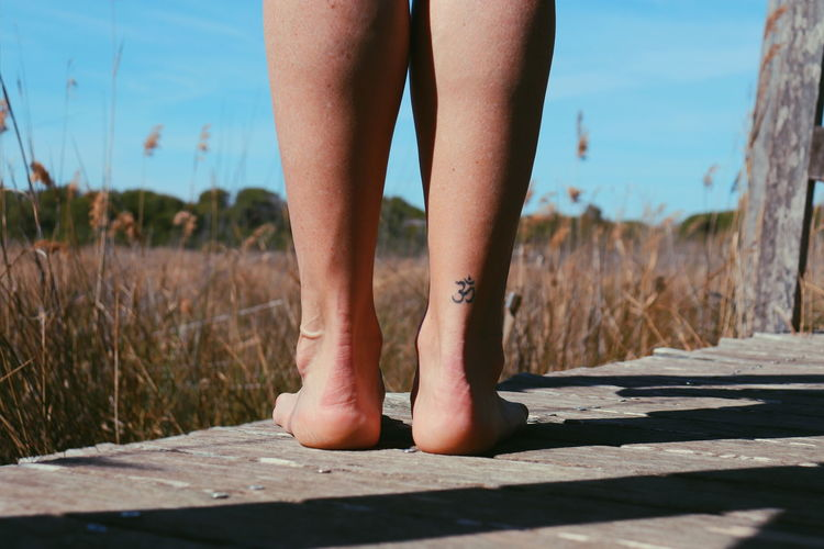 Low section of woman leg with tattoo on boardwalk