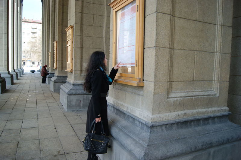Young woman reading notice on pillar