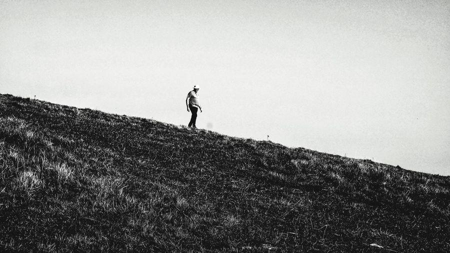 Side view of man walking on field against sky