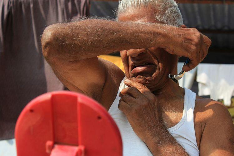 Close-up of senior man shaving while sitting outdoors