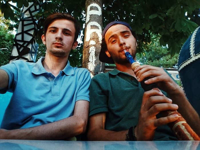 Low angle portrait of male friends sitting at table against tree