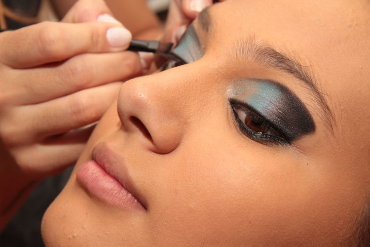 Close-Up Of Beautician Applying Make-Up On Woman
