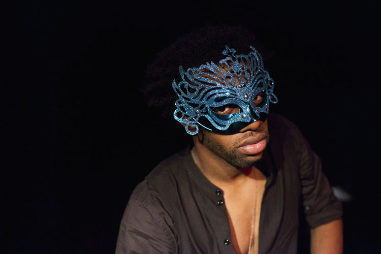 Portrait of young man wearing mask against black background