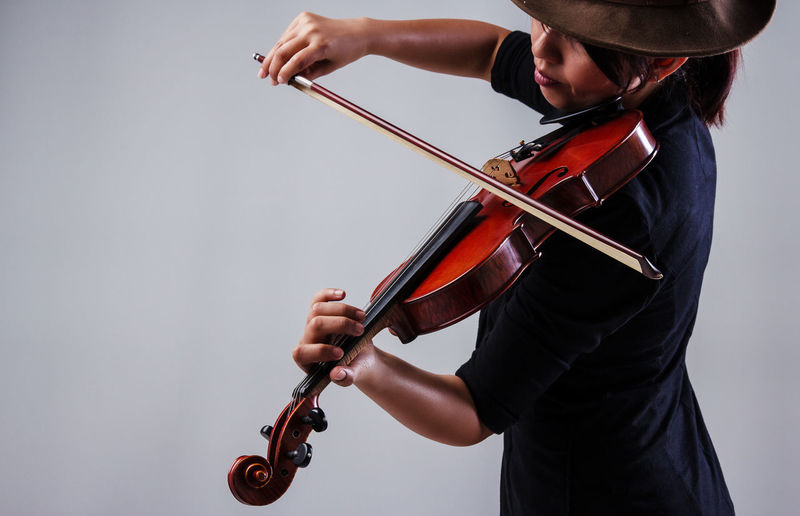 Woman Playing Violin Against Wall