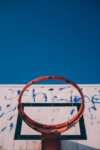 Low angle view of broken basketball hoop against clear blue sky