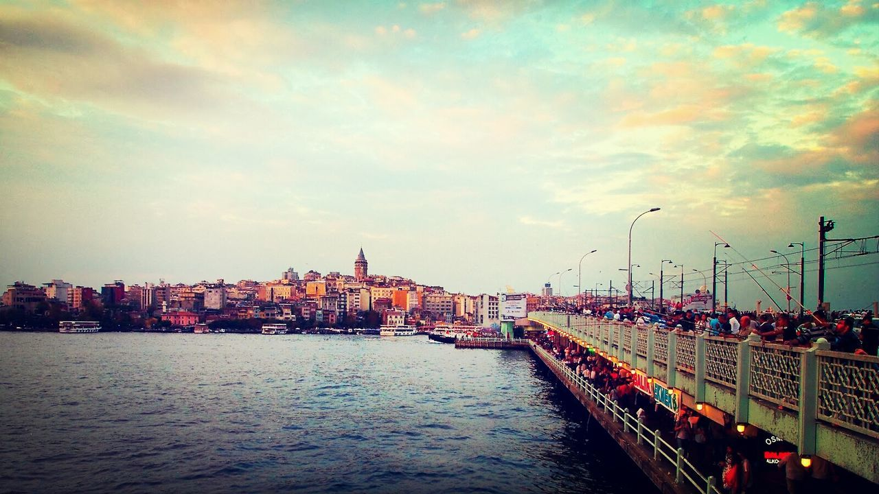 People fishing on Galata Bridge over river against cityscape