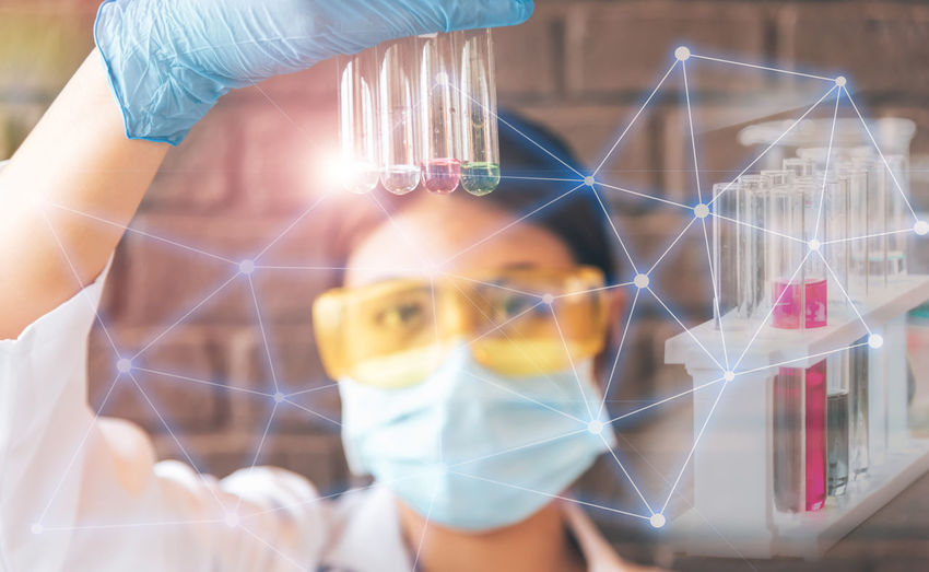 Digital composite image of scientist holding test tubes at laboratory