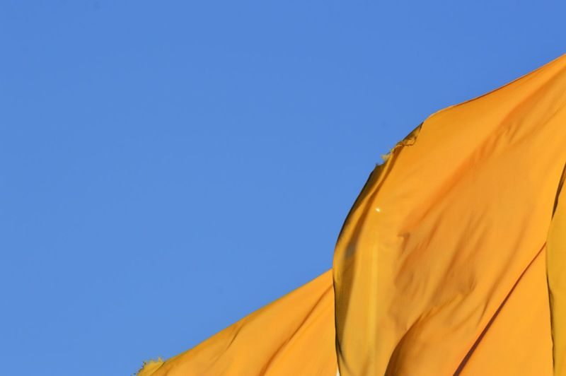 Low angle view of yellow flags against clear sky