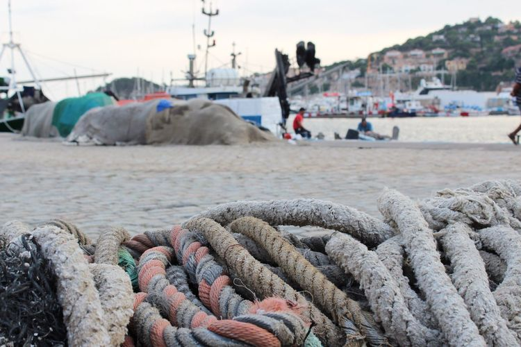 Visual Creativity Nautical Vessel Fishing Industry Rope Harbor Focus On Foreground Beach Incidental People Boat Sea Water Chain Fishing Net Commercial Dock Transportation Girona Gironamenamora Costa Brava SPAIN Travel Destinations Strength Close-up String Travel Live For The Story Rope Transportation Harbor Day Fishing