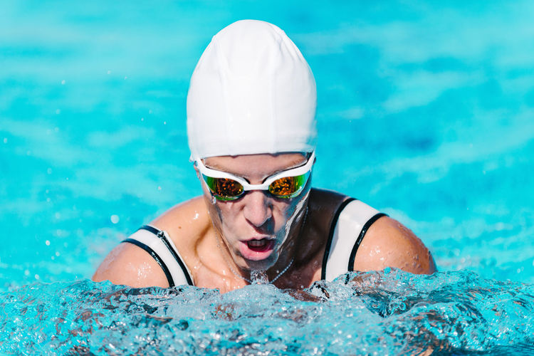 Female Swimmer on Training in the Swimming Pool Swimmer Female Water Sport Breaststroke Style Style Young Pool Competition Swimwear Athlete Goggles Training Swim Competitive Healthy Pepole Active Cap Swimming Swimming Pool Energy Exercise Professional Woman Strength Adult Muscular Lifestyle Activity Face Race Action Winner Motion Health Skill  Caucasian White Exercising Healthy Lifestyle Sports Training Beautiful Outdoors Blue One Person Turquoise Colored Front View
