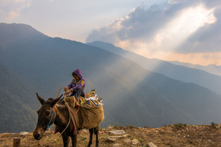 Boy riding horse on mountain against cloudy sky