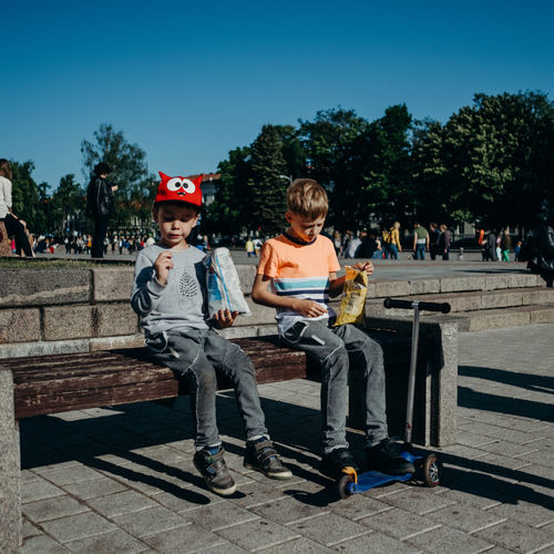Boys Casual Clothing Child Childhood Day Front View Full Length Incidental People Innocence Leisure Activity Lifestyles Males  Men Nature Outdoors People Real People Sitting Sunlight Togetherness Tree