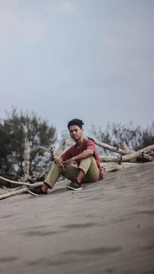 Portrait of man sitting on sand against sky