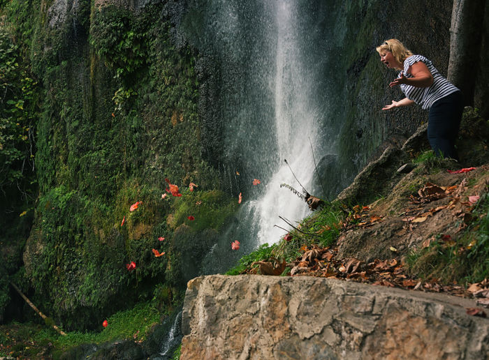 Surprised woman looking at autumn leaves falling by waterfall