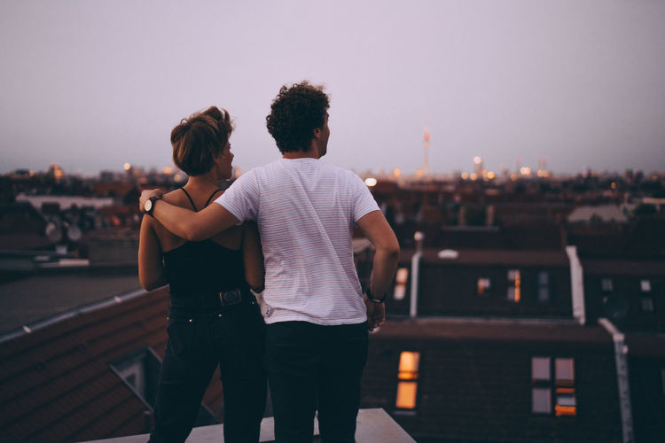 Rear view of couple standing against cityscape during sunset