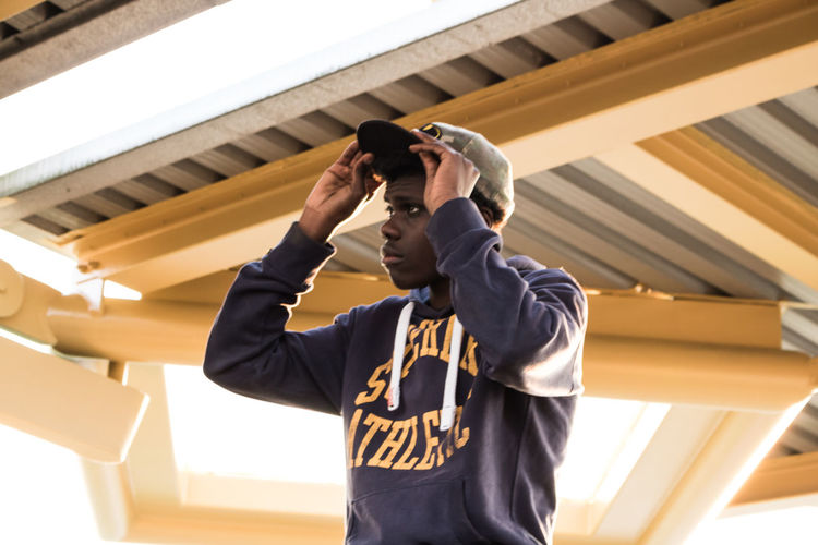 Young man wearing cap while looking away against ceiling