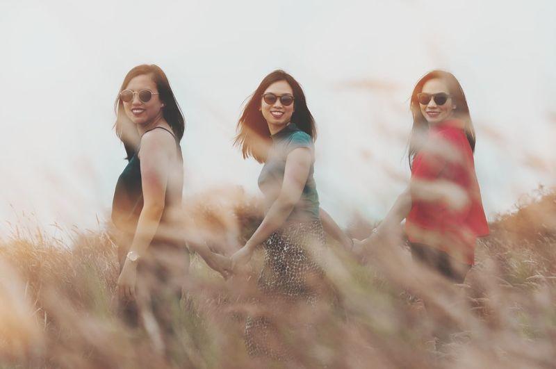 Young female friends walking on field seen through grass