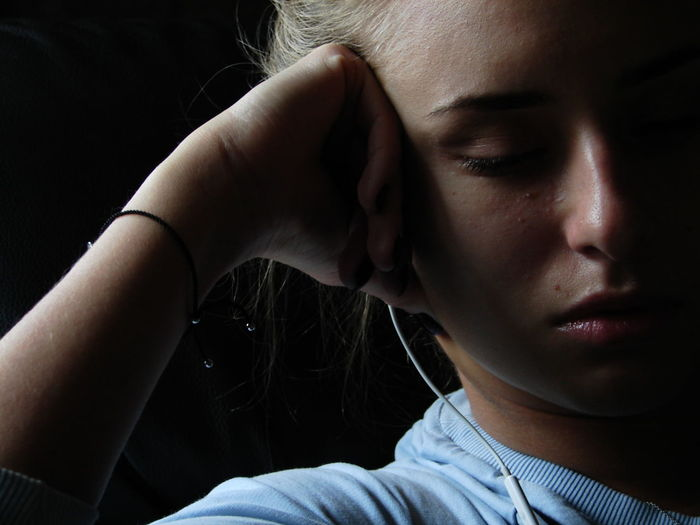 Close-up of young woman listening music on headphones
