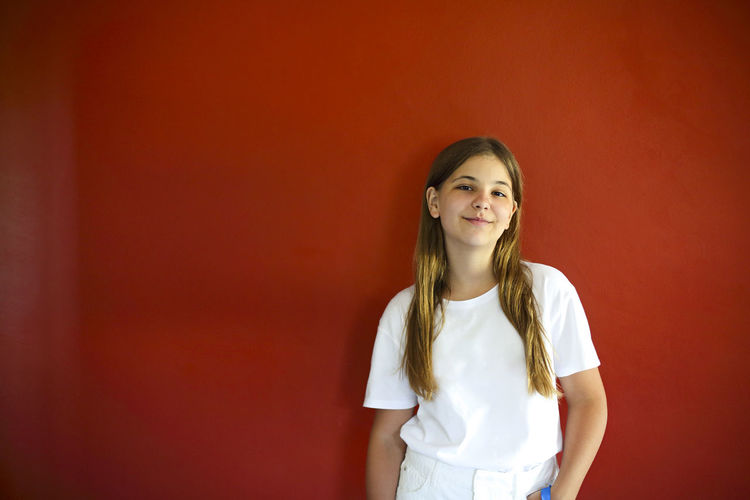 Portrait of smiling girl against red wall
