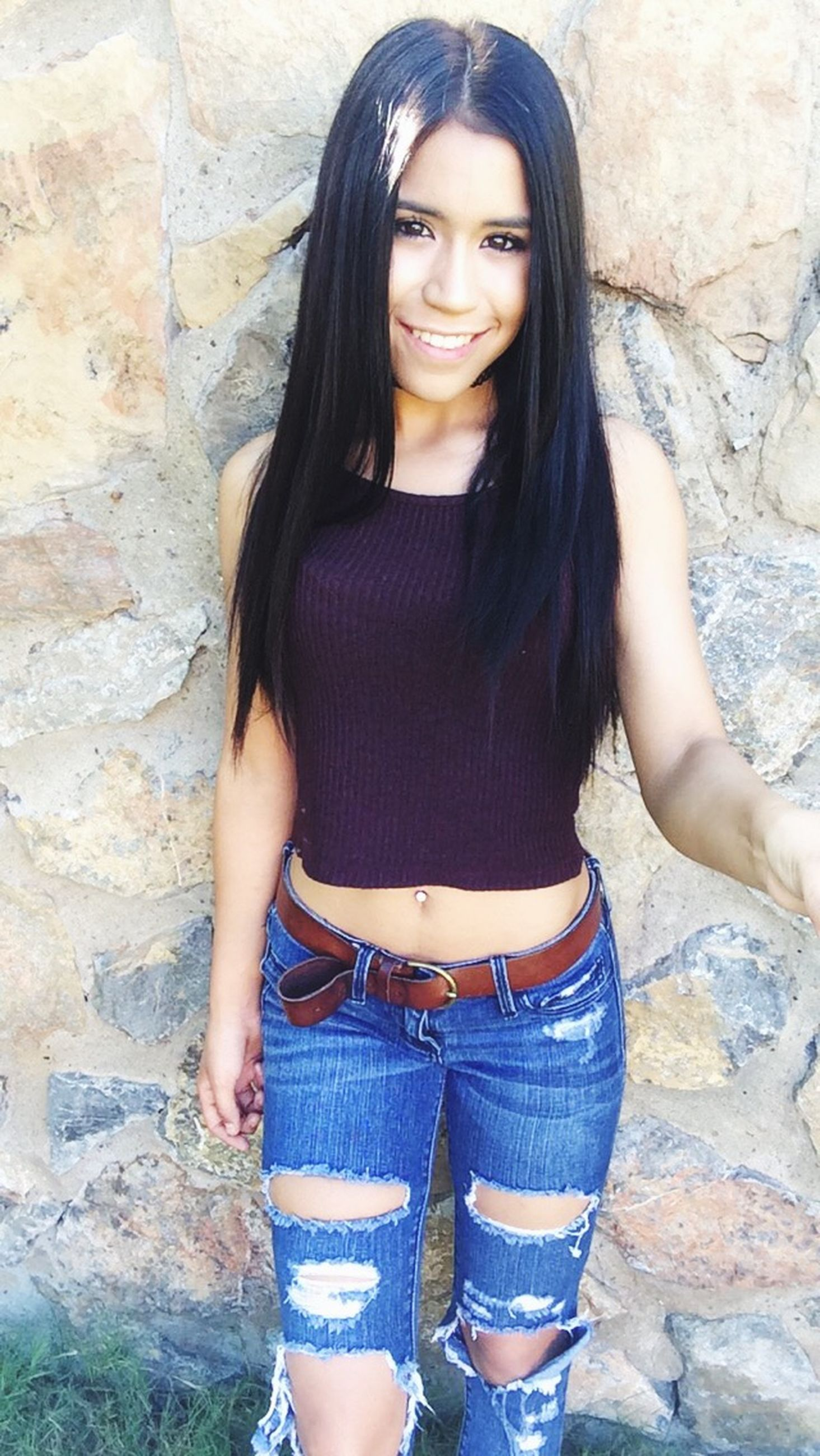 young adult, young women, portrait, looking at camera, person, lifestyles, front view, standing, casual clothing, long hair, three quarter length, leisure activity, wall - building feature, black hair, smiling, fashion, beauty