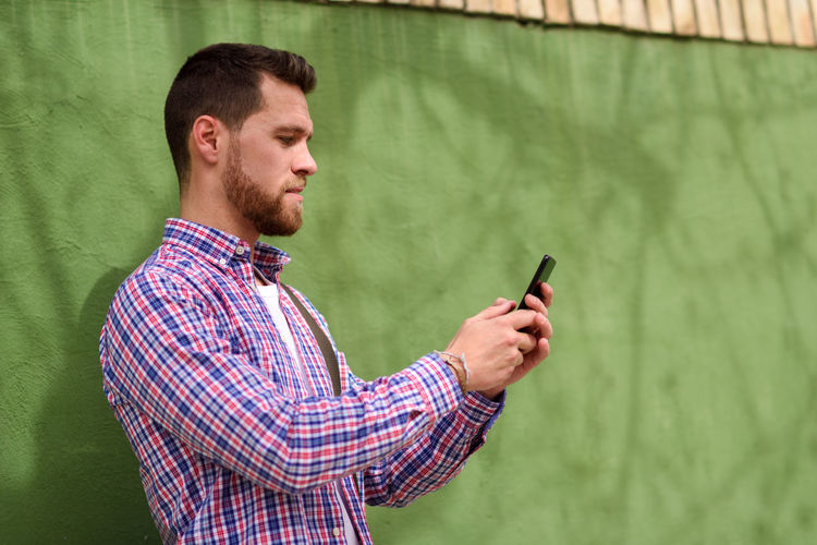 Young man looking his smart phone in urban background. Guy wearing casual clothes. Lifestyle concept. Adult Beard Brown Hair Communication Connection Facial Hair Green Color Hairstyle Holding Men Mobile Phone One Person Portable Information Device Technology Text Messaging Waist Up Wireless Technology Young Adult Young Men