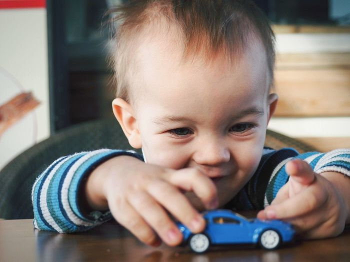 Cute boy playing with toy car at home