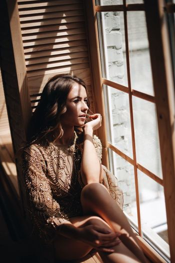 young beautiful girl by the window Young Adult One Person Window Real People Young Women Leisure Activity Lifestyles Indoors  Portrait Sitting Women Beautiful Woman Looking Three Quarter Length Clothing Beauty Contemplation Hair Hairstyle