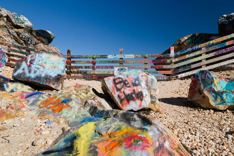 graffiti on the top of the Bell Mountain Bell Mountain GA Graffiti Perspective Top Architecture Blue Built Structure Clear Sky Day Fence Mountain Multi Colored No People Outdoors Pebbles Rocks Sky Stone Wide Angle