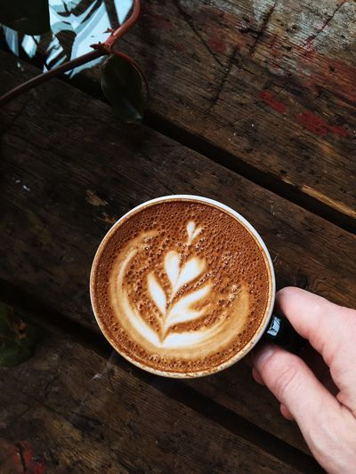 Male hand holding cup with coffee Latteart Coffee Coffee - Drink Drink Human Hand Cup Hand Coffee Cup Food And Drink Mug Frothy Drink Froth Art Human Body Part Table Hot Drink Refreshment Cappuccino High Angle View One Person Real People Creativity